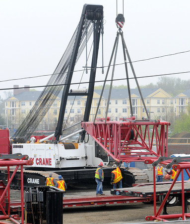 KEN YUSZKUS/Staff photo. Workers with the use of a crane assemble the large crane at the MBTA train station in Salem.         5/9/14