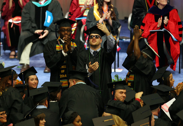 Salem State University graduates salute their families, thanking them for their support on Saturday afternoon during Commencement. . DAVID LE/Staff photo. 5/18/14.