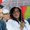 KEN YUSZKUS/Staff photo. Graduate Lyeisha Thompson uses an umbrella as the rain starts at the beginning of the Peabody Veterans Memorial High School graduation.   5/30/14.
