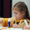 Five-year-old Skyler Thompson adds sequins to her piece of artwork at the Pajamas and Books program held at the Hamilton-Wenham Public Library on Tuesday evening. A program that runs every Tuesday evening from 6:30-7:15 is put on by the Coordinated Family and Community Engagement of Hamilton-Wenham. DAVID LE/Staff photo. 5/20/14