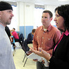 KEN YUSZKUS/Staff photo.  John Reed, left, who was displaced by the fire at 60 Dow Street in Salem speaks with Salem Mayor Kim Driscoll at the Salem Senior Center as director of constituent services Kristian Hoysradt listens.      5/6/14