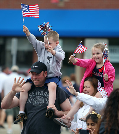 Brad and Jen Chase, of Danvers, wave to parade goers as their son Chris, 5, and niece MaKena Chase, also 5, sit on their shoulders and wave their flags during the annual Danvers Memorial Day Parade on Monday morning.DAVID LE/Staff photo. 5/26/14.