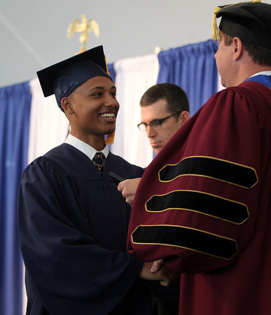 St. John's Prep graduate Josue Aviles shakes hands with Headmaster Edward Hardiman while receiving his diploma during Commencement on Sunday afternoon at Ryken Field in Danvers. DAVID LE/Staff photo. 5/18/14.