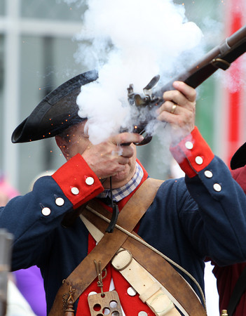 Bill Clemens is showered with smoke and a few embers as he fires off one of three rounds in Danvers Square as part of the annual Danvers Memorial Day Parade on Monday morning. DAVID LE/Staff photo. 5/26/14.