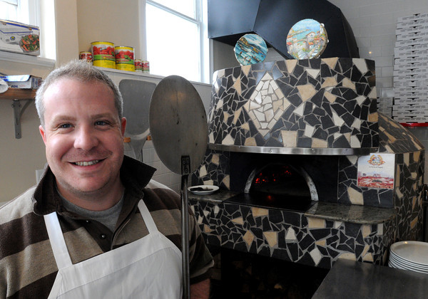 KEN YUSZKUS/Staff Photo.  Michael Magner stands near the pizza oven imported from Italy at his restaurant, Prides Piccola Napoletana in Beverly.   5/23/14.