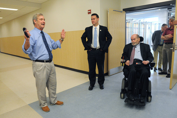 KEN YUSZKUS/Staff photo. Superintendent of Essex Tech Dan O'Connell, left, tours the new Essex Tech with Peabody Mayor Ed Bettencourt, center, and former Sen. Fred Berry, right. They are in one of the hallways,    5/20/14