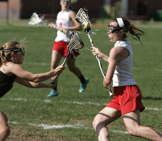 KEN YUSZKUS/Staff photo.  Ipswich's Claire Gardner, left, stands ready to defend against Masco's Meghan Collins during the Ipswich at Masconomet girls lacrosse game. 5/12/14