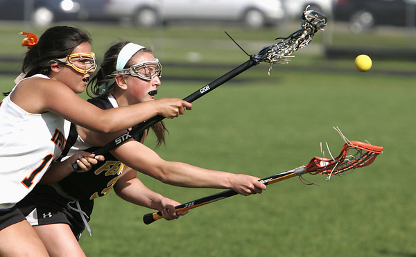 KEN YUSZKUS/Staff photo.  Bishop Fenwick's Jacqueline Hart, right, tries to regain possession of the ball as Ipswich's JoAnna Perry tries for the ball during the Bishop Fenwick at Ipswich High girls lacrosse North Division 2 quarterfinal playoff game.  5/29/14.