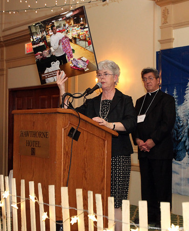 Virginia Doocy, Director of Catholic Charities North holds up a photo of St. Anne's Parish of Salem, during the presentation of the A Salute to Partnership award to Father Louis Bourgeois, representing the Parish, on Thursday evening at the Hawthorne Hotel during their annual Spring Gala. DAVID LE/Staff photo. 5/1/14