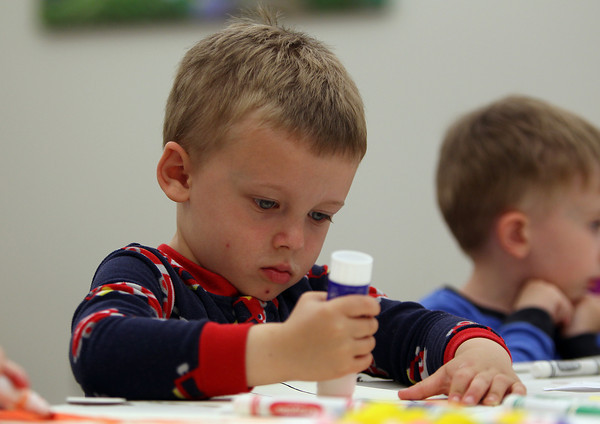 Owen Belliveau, 3, of Wenham, uses a glue stick to attack pompoms and sequins to his pajamas picture during the Pajamas and Books at the Hamilton-Wenham Public Library on Tuesday evening. A program that runs every Tuesday evening from 6:30-7:15 is put on by the Coordinated Family and Community Engagement of Hamilton-Wenham. DAVID LE/Staff photo. 5/20/14