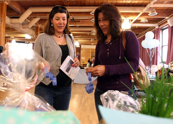 Jen Gagne, of Peabody, and Cheryl Casey, of Salem, choose different silent auction items to bid on at the second annual Bowditch Bash fundraiser held at the Moose Lodge in Salem on Friday evening. DAVID LE/Staff photo. 5/2/14
