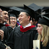 Gordon-Conwell graduate Kyuwok Kang laughs while talking with classmates prior to the start of Commencement on Saturday morning. DAVID LE/Staff photo. 5/10/14