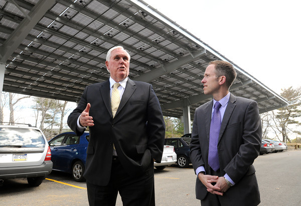 KEN YUSZKUS/Staff photo. Endicott College president Richard Wylie, left, speaks about Endicott College's new solar parking lot canopy which is partially shown in the background. Department of Energy Resources commissioner Mark Sylvia is on the right.   5/5/14
