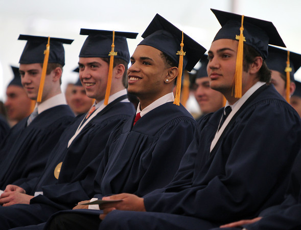 From left, St. John's Prep graduates David Arakelian Jr., Shemar Andujar, and Luke Andrew smile while listening to  during Commencement on Sunday afternoon at Ryken Field in Danvers. DAVID LE/Staff photo. 5/18/14.