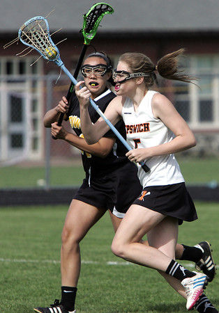 KEN YUSZKUS/Staff photo.  Bishop Fenwick's Emily Rocker slashes at the ball as Ipswich's Meghan Lindahl carries it toward the net during the Bishop Fenwick at Ipswich High girls lacrosse North Division 2 quarterfinal playoff game.  5/29/14.
