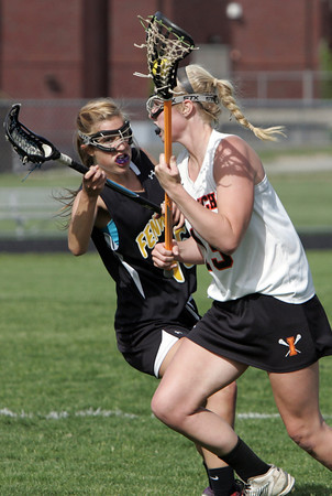 KEN YUSZKUS/Staff photo. Ipswich's  Jordan Morrissey, right, has the ball and is followed by Bishop Fenwick's Natalie Emerson during the Bishop Fenwick at Ipswich High girls lacrosse North Division 2 quarterfinal playoff game.  5/29/14.