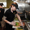 KEN YUSZKUS/Staff photo. Abby Obin, left, and Amy Gill prepare food in the kitchen at the Daily Harvest Cafe in Danvers.     5/5/14