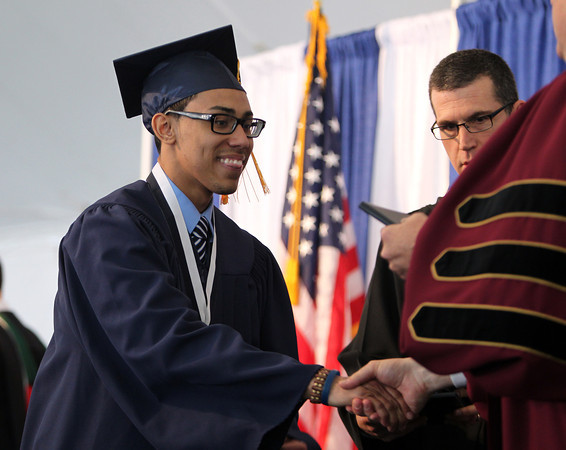 St. John's Prep graduate Danny Adames shakes hands with Headmaster Edward Hardiman while receiving his diploma during Commencement on Sunday afternoon at Ryken Field in Danvers. DAVID LE/Staff photo. 5/18/14.