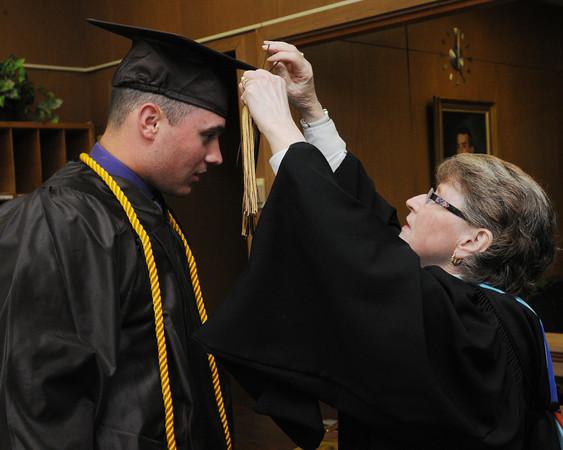 KEN YUSZKUS/Staff Photo. Grad James Traversy has Sister Geraldine help by adding the tassle before the start of the Bishop Fenwick graduation.  5/23/14.