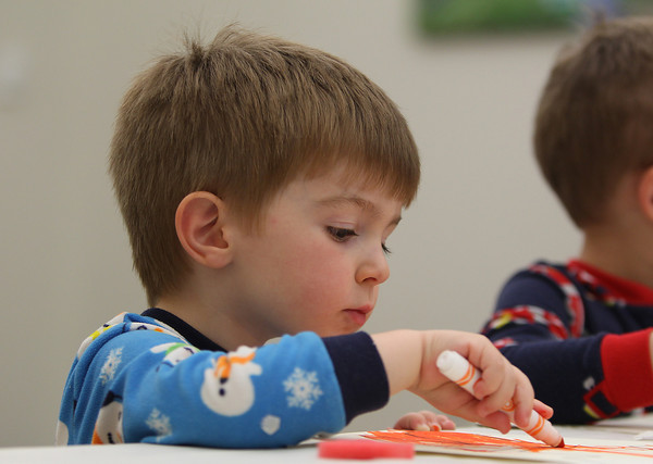 Three-year-old Owen Todd, of Hamilton, concentrates on coloring in his pajama picture during Pajamas and Books at the Hamilton-Wenham Public Library on Tuesday evening. A program that runs every Tuesday evening from 6:30-7:15 is put on by the Coordinated Family and Community Engagement of Hamilton-Wenham. DAVID LE/Staff photo. 5/20/14