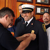 Captain Ted Quinn, of the Peabody Fire Department, pins a badge on the new uniform of Father Chris Foustoukos, of St. Vasilios Greek Orthodox Church on Wednesday afternoon in the Peabody Fire Station. Foustoukos is being appointed as the Peabody Fire Department's full-time volunteer chaplain. DAVID LE/Staff photo. 5/14/14.
