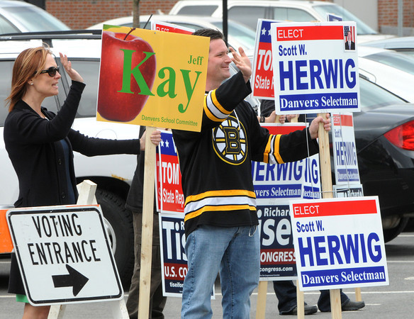 KEN YUSZKUS/Staff photo.  Kimberly Kay, left, and Scott Herwig wave to voters outside Danvers High School by the the gymnasium where they entered to vote.     5/6/14