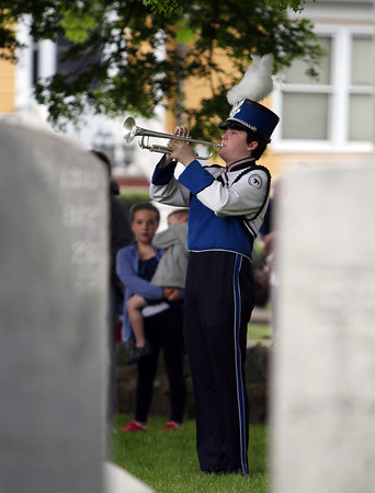 Danvers High School sophomore Brian Vaughan plays taps in the High Street Cemetery as part of the annual Danvers Memorial Day Parade on Monday morning. DAVID LE/Staff photo. 5/26/14.