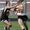 KEN YUSZKUS/Staff photo. Ipswich Jordan Morrissey, right, runs the ball as Bishop Fenwick's Nicole Muir tries to knock the ball out of her stick during the Bishop Fenwick at Ipswich High girls lacrosse North Division 2 quarterfinal playoff game.  5/29/14.