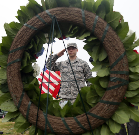 DAVID LE/Staff photo. Austin Bertrand, a Ssgt. of the International Guard salutes a wreath he just placed down at a short ceremony to honor all branches of the military on Sunday morning at St. Mary's Cemetery in Salem. 5/29/16.
