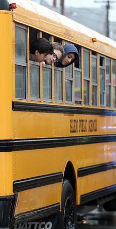 DAVID LE/Staff photo. A couple intrigued students stick their heads out the window to look at the damage down to their school bus after a minor crash on Thursday afternoon. A few students were taken by ambulance to the hospital. 5/5/16.