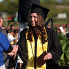DAVID LE/Staff photo. Bishop Fenwick graduate Sydney Brennan smiles while receiving a traditional yellow sunflower after receiving her diploma on Friday evening. 5/20/16.