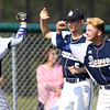 DAVID LE/Staff photo. Danvers junior Jordan DeDonato (13) gets greeted by junior Zach Turner (5) and senior Danny Lynch (7) after he came across the plate with one of the Falcons three 1st inning runs. 5/27/16.
