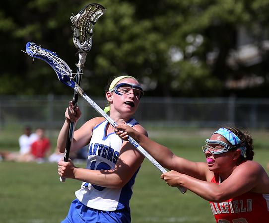 KEN YUSZKUS/Staff photo.          Danvers' Olivia Heutlinger, left, passes to a teammate during the Wakefield at Danvers girls lacrosse tournament game.            05/31/16