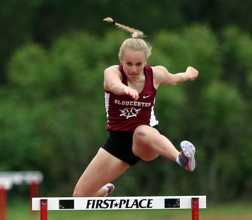DAVID LE/Staff photo. Gloucester's Chloe Kenyon leaps over the final hurdle and out-races Marblehead's Clara Pollard to the finish line to capture first place in the 400 meter hurdles on Tuesday afternoon. 5/24/16.