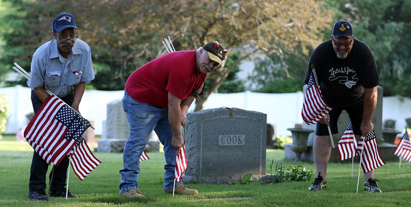 DAVID LE/Staff photo. Arnold Barclay, Rich Greenlaw, and Keith Martin, volunteers from Danvers placed flags around Walnut Grove Cemetery on Wednesday afternoon in preparation for Memorial Day celebrations. 5/25/16.