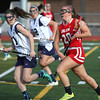 KEN YUSZKUS/Staff photo.   Peabody's Carla Patania, left, runs along side of Salem's Jessica Jellison at the Salem at Peabody girls lacrosse game.       04/29/16