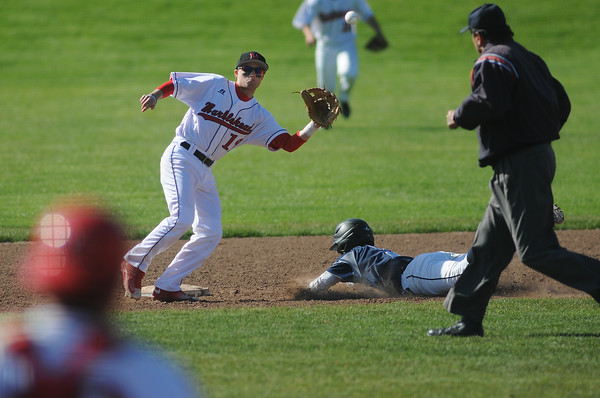 PAUL BILODEAU/Staff photo. Marblehead's shortstop Tim Kalinowski eye the ball as Peabody's Jake Gustin slides safely into second base during Magicians' game against the Tanners at Seaside Park in Marblehead.