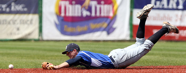 DAVID LE/Staff photo. Danvers senior shortstop Andrew Olszak can't manage cleanly field the ball after an all out layout. 5/14/16.