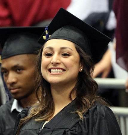 DAVID LE/Staff photo. A North Shore Community College graduate smiles at her family as she marches into commencement on Thursday evening. 5/26/16.