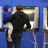 KEN YUSZKUS/Staff photo.     While holding her son Teddy, 2 1/2, Pia Freeley votes at Danvers High School.     05/03/16