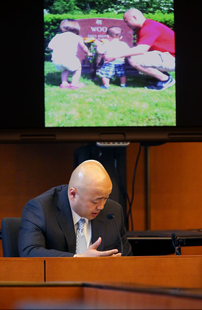 KEN YUSZKUS/Staff photo.      Edwin Woo, son of the murdered Ipswich restaurant owner, gives his impact statement at Salem Superior Court with the projected image of the grave in back of him.    05/19/16