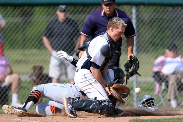 DAVID LE/Staff photo. Danvers junior catcher Matt Andreas drops to a knee to block a short-hopped throw as Beverly junior Luke Samperi slides in safely behind him to score one of three runs for the Panthers. 5/27/16.