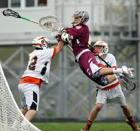 DAVID LE/Staff photo. Newburyport senior captain Will Fogel leaps in the air and tries to sneak the ball past  Ipswich sophomore goalie Aidan McAdams (12) during the third quarter of play. 5/13/16.