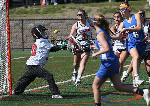 KEN YUSZKUS/Staff photo.   Marblehead's goalie Brittany Lydon, left, defends the net as Danvers' Allie Zunick takes a shot during the Danvers at Marblehead girls lacrosse game at Marblehead High School.     05/16/16