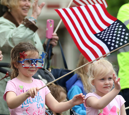 DAVID LE/Staff photo. Sisters Grace, 6, left and Annie Moran, 4, right, of Salem, excitedly watch the parade while waving and bearing an American flag at the annual Beverly Memorial Day Parade on Monday afternoon. 5/30/16.