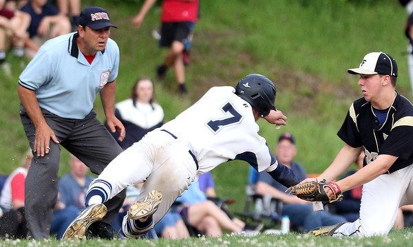 DAVID LE/Staff photo. Peabody sophomore Jake Gustin somehow manages to slide around a tag by Bishop Fenwick third baseman Cody Bright on a pickoff play at third. 5/30/16.