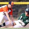 DAVID LE/Staff photo. Manchester-Essex shortstop Hunter Flood slides safely through the legs of Ipswich shortstop Liam Sullivan while the ball skips away as Flood advanced to second on a throw to the plate. 5/17/16.