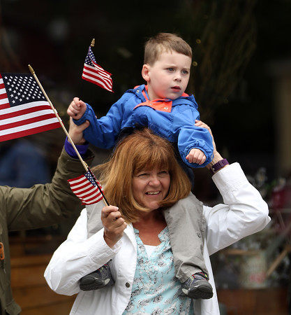 DAVID LE/Staff photo. Three-year-old Jake Nickerson sits on his grandmother Debbie Casey's shoulders, while watching the annual Beverly Memorial Day Parade on Monday afternoon. 5/30/16.