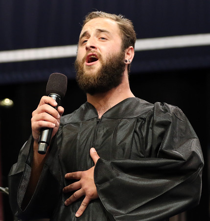 DAVID LE/Staff photo. North Shore Community College graduate Kevin Evangelista, of Boxford, sings the National Anthem at the start of the Commencement exercises on Thursday evening. 5/26/16.