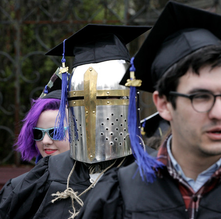 KEN YUSZKUS/Staff photo.    The Montserrat College of Art graduate Johnathan Good wears a helmet during the processional to enter The Cabot at the start of their commencement ceremony.     05/13/16
